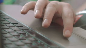 Close-up of a human's hand typing and touching a laptop keyboard. In full HD stock footage