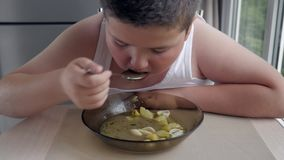 Close up hungry fat kid boy with appetite eats soup in kitchen, concept of medicine and health. overweight in children sedentary l stock video footage