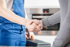 Specialist shaking hands with housewife. Close-up of hydraulic specialist in blue overalls shaking hands with a housewife after repairing a glitch Royalty Free Stock Photography