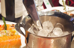 Close-Up of Ice in Bucket with Tongs on Food Cart Stock Photo