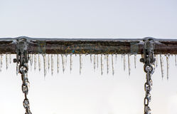 Close Up of Ice Covered Swing Bar and Chains Royalty Free Stock Photography