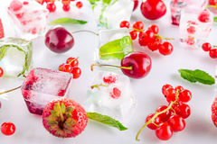 Close up ice cubes with fresh berries among not frozen cherry, strawberry and mint leafs on the white background. Selective focus Royalty Free Stock Photos