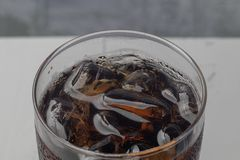 Iced cola in glass on the table. Close up of iced cola in glass on the table stock photo