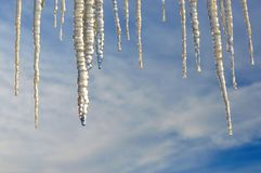 Close up of icicles. Abstract. Hanging icicles with very interesting shape and texture. Blue sky and clouds in the background. Some room for text royalty free stock photos