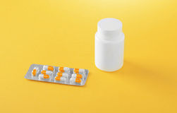 Close-up of icons of medication on a bright yellow background. Brilliant blisters with white and orange capsules. Stock Photography