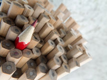 Close up of identical graphite pencils and one different red  cr Royalty Free Stock Photos