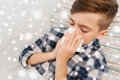 Close up of ill boy lying in bed and blowing nose Stock Images