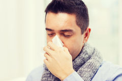 Close up of ill man with flu blowing nose at home Stock Image