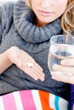 Close-up of an ill woman holding pills and water Stock Image