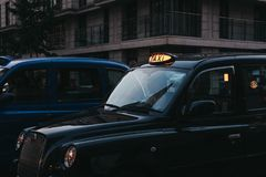 Close up of an illuminated taxi sign on a black cab in London, UK. London taxis are an important part of the capital`s transport system royalty free stock photography