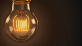 Close up of an illuminated vintage hanging light bulb over dark stock illustration