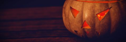 Close up of illuminated jack o lantern on table during Halloween. Close up of illuminated white jack o lantern on table during Halloween Stock Photography