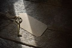Antique Metal House Keys and Brown Label. A close up image of an antique brass house key with brown label Royalty Free Stock Images