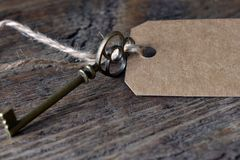 Antique Metal House Keys and Brown Label. A close up image of an antique brass house key with brown label Royalty Free Stock Image