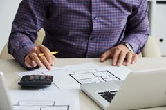 Calculating cost. Close-up image of architect caculating estimated construction cost Royalty Free Stock Image