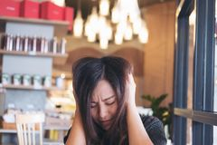 Close up image of an Asian woman close her eyes with feeling stress. And upset in restaurant Royalty Free Stock Photo
