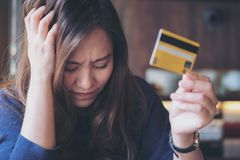 Asian woman close her eyes while holding credit card with feeling stressed and broke. Close up image of an Asian woman close her eyes while holding credit card Stock Photo