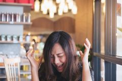 Close up image of an Asian woman close her eyes and scream with feeling angry. In restaurant Royalty Free Stock Images