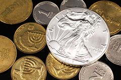 A close up image of an assortment of Israeli coins with an American silver coin on a black background. A macro image of miscellaneous coins from Israel with an royalty free stock photo
