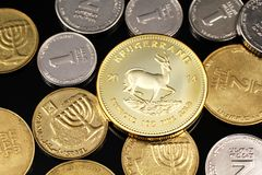 A close up image of an assortment of Israeli coins with a gold South African krugerrand on a black background. A macro image of miscellaneous coins from Israel stock images