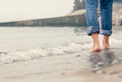 Close up image barefoot man legs in the sea surf Stock Photos