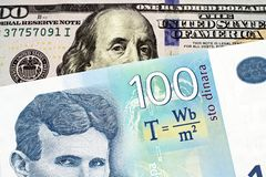 A blue one hundred Serbian dinar bank note with an American one hundred dollar bill. A close up image of a blue one hundred Serbian dinar bank note with an stock photos
