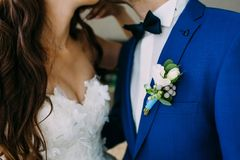 Close-up image of a Boutonniere on the groom`s jacket. Blurred bride and groom are kissing. Artwork Stock Images