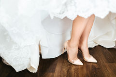 Close-up image of bridal beige shoes stands on a wooden floor. Stock Image