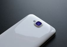 Close Up Image of the Camera of White Smart Phone on Black Table Stock Images