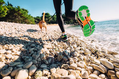Close up image canicrosser legs in run shoes on the sea coast Royalty Free Stock Photos