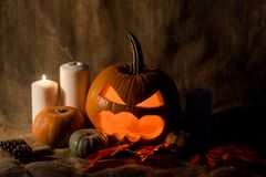 Scary jack-o-lantern, red leaves and candles Royalty Free Stock Photography