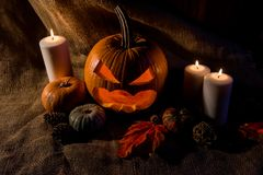 Scary jack-o-lantern, red leaves and candles Stock Photos