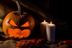 Scary jack-o-lantern, red leaves and candles Royalty Free Stock Image