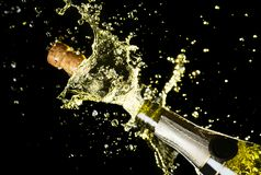 Close up image of champagne cork flying out of champagne bottle. Celebration theme with explosion of splashing champagne sparkling. Wine on black background stock photo
