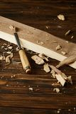 Close up image of chisel and wooden pieces on brown table royalty free stock photos