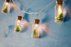 Close up image of Christmas tree in the masson jar garland light over wooden blue background. Close up image of Christmas tree in the masson jar garland light stock photos