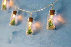 close up image of Christmas tree in the masson jar garland light over wooden blue background. royalty free stock photos