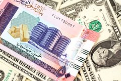 A fifty Sudanese pound note with American one dollar bills. A close up image of a colorful fifty pound bank note from Sudan on a background of American one stock photography