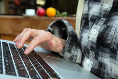 Close up Image of Computer and Hand of Person touching keyboard. Of Laptop Hotel Cafe Interior on Background Casual Clothing Royalty Free Stock Photography