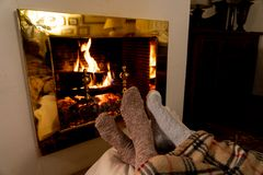 Happy couple relaxing under blanket by the fireplace warming up feet in woolen socks. Close up image of couple sitting under the blanket by cozy fireplace stock image