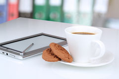 Close up image of cup of coffee with cookies. digital tablet on Stock Photos