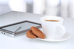Close up image of cup of coffee with cookies. digital tablet on Royalty Free Stock Photography