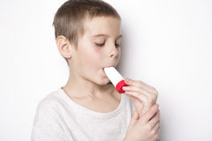 Close up image of a cute little boy using inhaler for asthma. A Close up image of a cute little boy using inhaler for asthma Royalty Free Stock Images