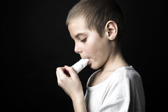 Close up image of a cute little boy using inhaler for asthma. Royalty Free Stock Photos