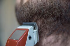 Close up young man shaving with electric razor Royalty Free Stock Photos