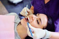 Dentist examining female`s teeth in dentistry. stock photography