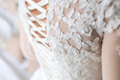Image of the detailed laces on the back of a wedding dress. Soft fous on lace. Close-up image of the detailed laces on the back of a wedding dress. Soft fous on Royalty Free Stock Images