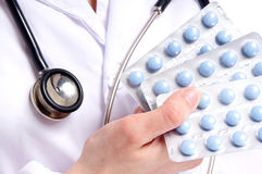 A close-up image of a doctor holding blue pills. A close-up image of a doctor in a white dress with a stethoscope holding three packs of blue pills. The image is Royalty Free Stock Photo