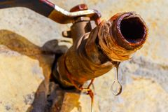Close up image of a drop of water dripping from a rusty tap royalty free stock images