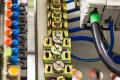 Close-up image of electrical wires is connected to cuprum clamps in power system of direct voltage with electrical stock photo